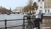 atmosfera : 4K European man with bicycle on a river bridge. Casual stylish male types on smartphone and looks around enjoying view. Vídeos