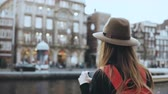 блог : Tourist lady takes photos of old architecture. Girl with long hair and red backpack enjoying amazing city scenery. 4K. Стоковые видеозаписи