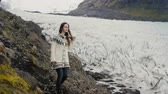 chlad : Young traveling woman walking through the rocks in the mountains, exploring the Vatnajokull glaciers lagoon in Iceland. Dostupné videozáznamy