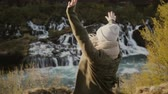 elevação : Back view of young beautiful woman standing near the waterfall and raising hands up, feeling freedom and happy.