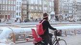 ingázó : Female blogger rides bicycle along a river quay. Tourism. Caucasian girl in hat on a city bike. Side view slow motion. Stock mozgókép