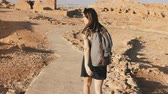 sedento : Woman with backpack explores ancient desert ruins. Beautiful European tourist walks on rocks and sand. Masada Israel 4K.