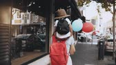 local : Mother carries son on shoulders along the street. Girl walks with a little happy kid in hat and two air balloons. 4K. Vídeos
