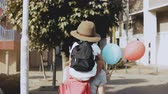 local : Mother carries son on shoulders among houses. Woman walking with a kid in hat and two air balloons. Lifestyle 4K.