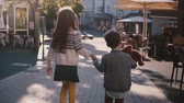 local : Two kids walk together, hold hands. Slow motion. Back view. Little children explore old town streets on a sunny day.