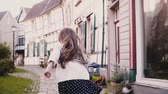 metade : Little girl looks at camera, runs on paved road. Back view. Slow motion. Cute European child running in old street.