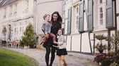 half timbered : Pretty woman walks together with two kids. Slow motion. European family. Mother, boy and girl hold hands. Togetherness. Stock Footage
