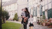 ходить : European family walk together. Mother and two kids. Slow motion. Woman, boy and girl hold hands smiling. Love and care.