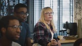 зависать : Multi-ethnic serious students at a meeting. Slow motion. Serious Caucasian girl in glasses listens carefully with drink