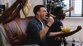ponto : African American friends watch sports on TV. Slow motion. Fans celebrate goal excited on the couch with popcorn. Emotion Stock Footage