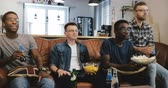 beisebol : African American male friends watch sports on TV. Multi ethnic geeky fans concentrated and serious on couch with popcorn Stock Footage