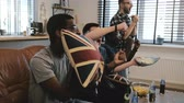 celebração : Mixed race male supporters watch sports on TV 4K. Fans celebrate goal victory holding British flag cushion. Slow motion.