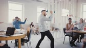 мотивированы : Camera follows happy businessman walk into office, doing funny celebration dance. Multi-ethnic workers laugh and clap 4K