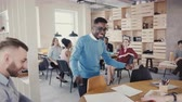 мотивированы : Happy African American man gives high fives to office colleagues. Celebrating business success with joyful dance 4K.