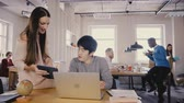 participation : Female boss gives instructions to Asian man. Multiethnic colleagues work in casual modern loft office, panning right 4K Stock Footage