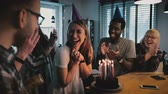parabéns : Happy Caucasian girl makes a wish at birthday cake with candles. Multiethnic friends at surprise party slow motion.