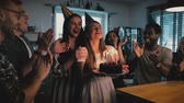 diverso : Happy Caucasian girl holding birthday cake, making a wish at cheerful fun multiethnic party with friends slow motion 4K.