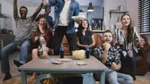 ganhar : Diverse group of friends watching sports on TV Football supporters celebrate success with popcorn and drinks. Emotion 4K Stock Footage