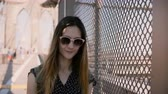 inclinar : Beautiful female tourist in sunglasses smiling, leaning to shadow net fence at Brooklyn Bridge, walking to camera 4K.