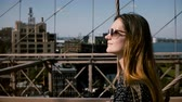 sunny side up : Camera follows beautiful happy European brunette businesswoman in stylish sunglasses walking along Brooklyn Bridge 4K.