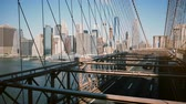 visto : Timelapse panoramic shot of New York seen through Brooklyn Bridge cables. Downtown buildings background on sunny day 4K.