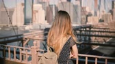 известный : Young female Caucasian tourist in stylish sunglasses with backpack standing alone at Brooklyn Bridge, New York City 4K.