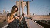 mensageiro : Beautiful smiling European blogger woman in stylish sunglasses using smartphone app at Brooklyn Bridge, walking away 4K.