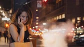 kultura mládeže : Young happy woman with bags standing in traffic downtown in the evening and talking on mobile phone in new York, America Dostupné videozáznamy