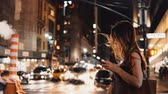 вид транспорта : Young beautiful woman standing in the evening in traffic downtown and using the smartphone in New York, America. Стоковые видеозаписи