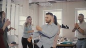 entreter : Young European businessman dancing together with colleagues at fun casual office party, celebrating career promotion 4K. Stock Footage