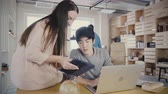 diverso : Beautiful female executive helps Asian colleague at his table. Multiethnic business people work in modern office 4K.