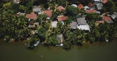 coco : Aerial view drone descending over lovely tropical coast resort hotels on a jungle river bank with lush green palm trees.