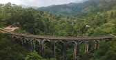 trilho : Drone flying backwards and rising to reveal breathtaking panoramic aerial view of Nine Arch Bridge Ella in Sri Lanka.