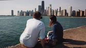 Чикаго : Back view of young couple having picnic on the shore of Michigan lake in Chicago, America. Man takes photo on smartphone Стоковые видеозаписи