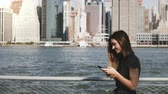 Beautiful young Caucasian woman with long hair walking along New York skyline panorama using smartphone on a sunny day.