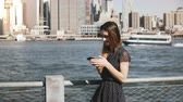 Beautiful young Caucasian girl with long hair walking along New York, Manhattan skyline making a phone call and talking.