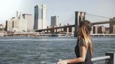 Happy relaxed smiling Caucasian girl with long hair walking along Manhattan skyline view talking on phone on a sunny day