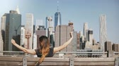 вид : Back view of happy female traveler with long hair blowing in the wind enjoying amazing Manhattan skyline view on a bench