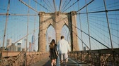 simetria : Romantic couple walk along Brooklyn Bridge NYC, hold hands and kiss on a beautiful summer day, back view low angle 4K.