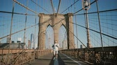 Happy European man with backpack walks by camera on a sunny day, looks around on the way to work at Brooklyn Bridge 4K.