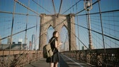 Young European female tourist with backpack walking along Brooklyn Bridge, New York and looking at smartphone 4K.