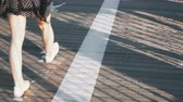simetria : Camera follows female legs walking along asphalt and wooden road with stripes, covered with beautiful thin shadows 4K.