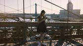 Beautiful Caucasian blogger woman using smartphone app at Brooklyn Bridge riverside panorama, then walking away 4K.