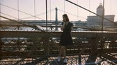 Happy Caucasian girl talking on phone, standing near amazing Brooklyn Bridge, New York view on a beautiful summer day 4K