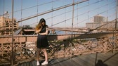 Pretty smiling Caucasian flirty girl talking to friend on the phone at Brooklyn Bridge, slowly walking back and forth 4K Wideo