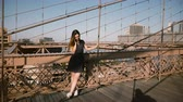 Attractive European young woman talking on phone, standing at amazing Brooklyn Bridge view on a beautiful summer day 4K