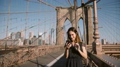 Attractive adult European woman talks to friends using smartphone video call app at Brooklyn Bridge, New York city 4K.