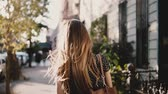 Back view happy Caucasian girl with flying hair walking along sunny city street, living casual lifestyle slow motion. Стоковые видеозаписи