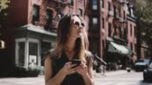 Beautiful Caucasian girl standing near famous old red brick New York City buildings, using smartphone app slow motion. Стоковые видеозаписи