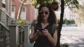 Happy Caucasian female tourist smiling, walking along beautiful old red brick buildings, using smartphone slow motion.